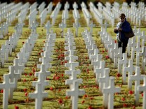A woman walks among the tombstones at the cemetery outside the WWI Douaumont Ossuary near Verdun