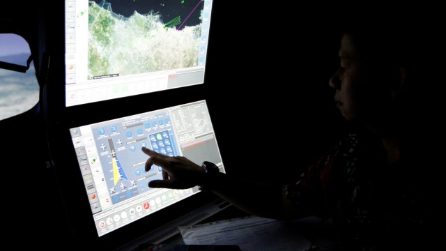 A senior pilot of Lion Air Group points at the control computer during a routine practice session on Boeing 737-900ER simulator at Angkasa Training Center near Jakarta