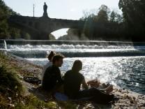 Münchner sitzen an der Isar unterhalb der Maximiliansbrücke nahe dem bayerischen Landtag