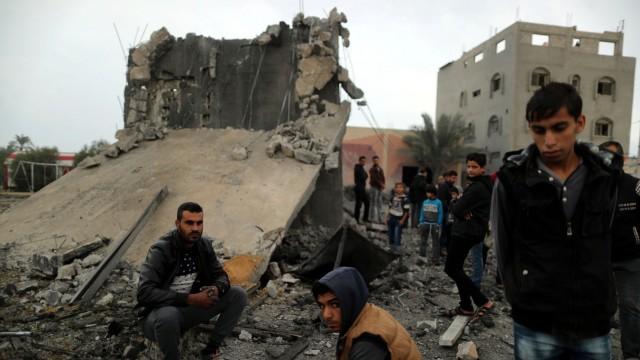 Gazastreifen - Palästinenser vor einem zerstörten Haus