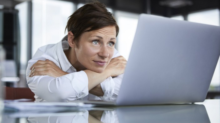 Businesswoman leaning on glass table in office looking at laptop model released Symbolfoto property