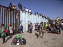 Flüchtlinge auf dem Grenzzaun zwischen Mexiko und den USA
