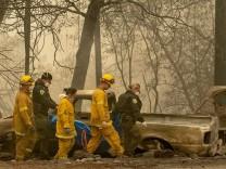 Waldbrände in Kalifornien - Feuerwehrleute vor verbranntem Wald