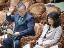 Yoshitaka Sakurada hebt bei einem Termin im japanischen Parlament die Hand.