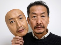 REAL-f Co. President Osamu Kitagawa shows off a super-realistic face mask at his factory in Otsu