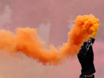 Protester holds a smoke safety flare during the May Day labour union march in Paris