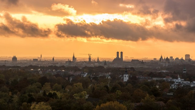 Dämmerung mit Wolken über dem Münchner Stadtteil Bogenhausen im Hintergrund die Frauenkirche Sonnen