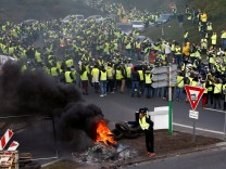 Protesters wearing yellow vests, a symbol of a French drivers' protest against higher fuel prices, attend a demonstration at the entrance of a shopping center in Nantes