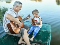 Grandfather teaching grandson playing guitar model released Symbolfoto PUBLICATIONxINxGERxSUIxAUTxH