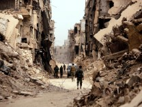 FILE PHOTO: Soldiers walk past damaged buildings in the Yarmouk Palestinian camp in Damascus