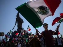 A boy waves Mexican flags as hundreds gather around the Cuauhtemoc Monument to protest against migrants from Central America in Tijuana, Mexico