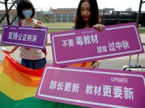 Supporters hold a rainbow flag and signs near the courthouse before the hearing in which a Chinese student lodged a suit against the Ministry of Education over school textbooks describing homosexuality as a mental disorder, in Beijing