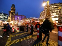 People walk through security barriers next to the site of the Christmas market's truck attack at Breitscheidplatz square in Berlin
