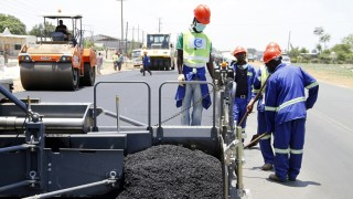 Labourers carry out surfacing work on a road near the Zambian capital Lusaka