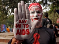 A man poses as he displays his hand and face painted with messages during an HIV/AIDS awareness campaign on the eve of World AIDS Day in Kolkata
