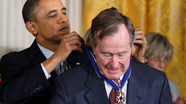 FILE PHOTO: U.S. President Barack Obama awards the Medal of Freedom to former U.S. President George H.W. Bush during a ceremony at the White House in Washington