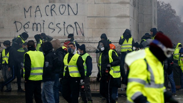 The message 'Macron Resign' is seen on the Arc de Triomphe as protesters wearing yellow vests, a symbol of a drivers' protest against higher diesel taxes, demonstrate at the Place de l'Etoile in Paris