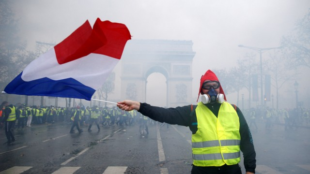 Protesters wearing yellow vests, a symbol of a French drivers' protest against higher diesel taxes, face off with French gendarmes during clashes at the Place de l'Etoile in Paris