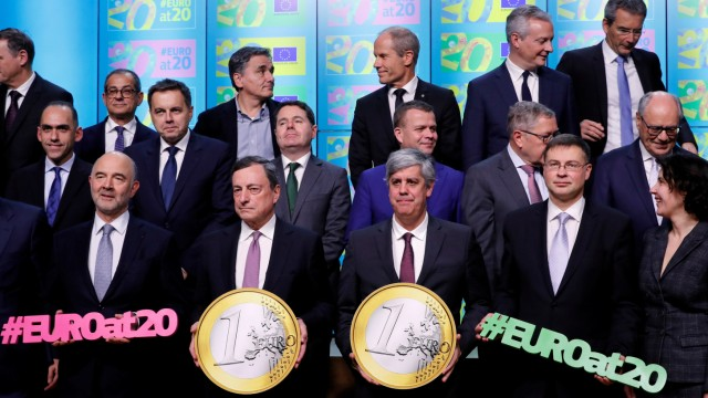 ECB President Draghi and eurozone finance and economy ministers take part in a group photo while celebrating the 20th anniversary of the euro during a eurozone finance ministers meeting in Brussels