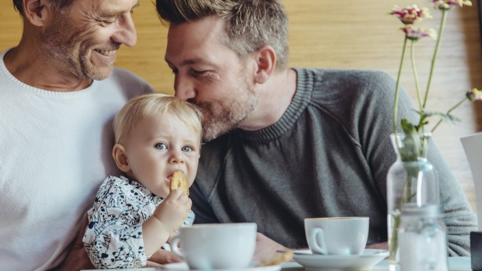 Gay couple cuddling with their baby in cafe model released Symbolfoto property released PUBLICATIONx