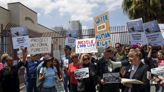 Demonstrators march outside a Nestle water bottling plant in Los Angeles, California