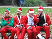 Revellers dressed as Santa Claus take a break during the annual SantaCon event in central London