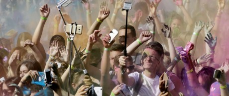 People take a selfies as they throw colors in the air during a Holi color festival in Riga