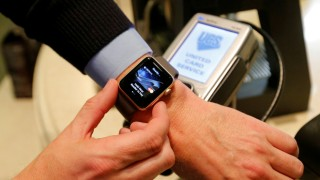 FILE PHOTO: Man uses Apple Watch to demonstrate mobile payment service Apple Pay at cafe in Moscow