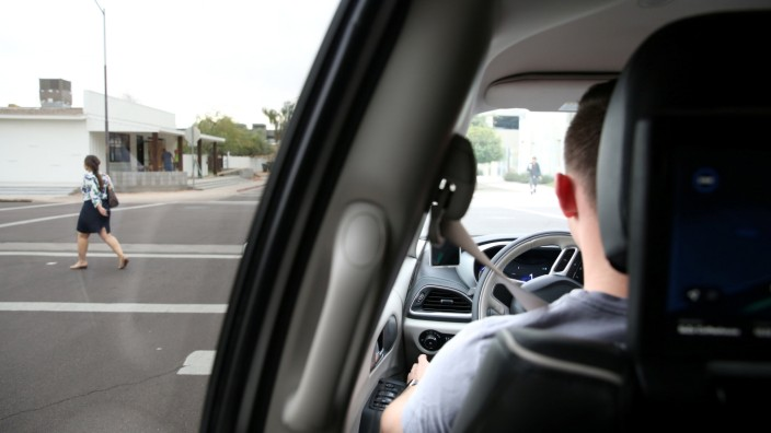Waymo Trained Driver Derek Sirakis looks out the windshield as the car stops for pedestrians during a demonstration in Chandler, Arizona