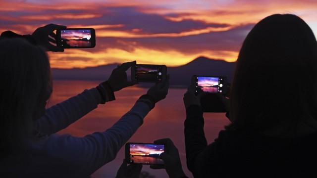 Menschen fotografieren den Sonnenuntergang mit ihrem Smartphone bei Luino Lago Maggiore Lombardei