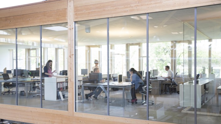 Team of five business people at workplaces in modern office model released property released PUBLICA