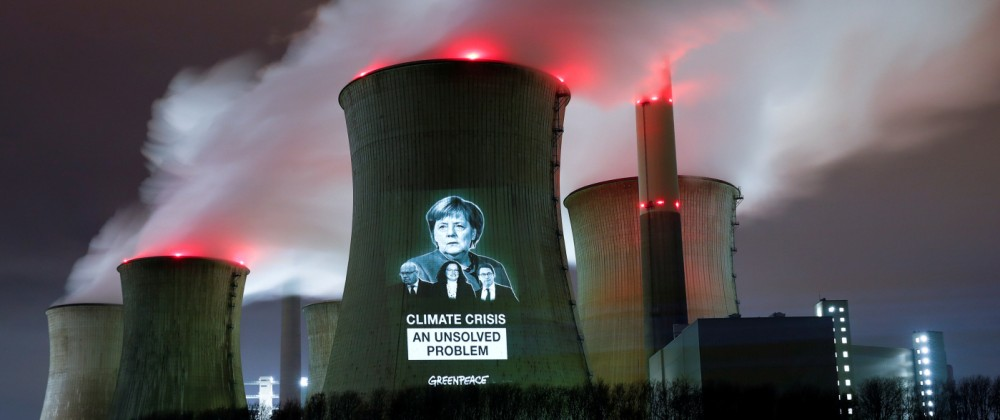 Greenpeace activists project images of German politicians with a slogan onto a cooling tower of the brown coal power plant of RWE, in Neurath