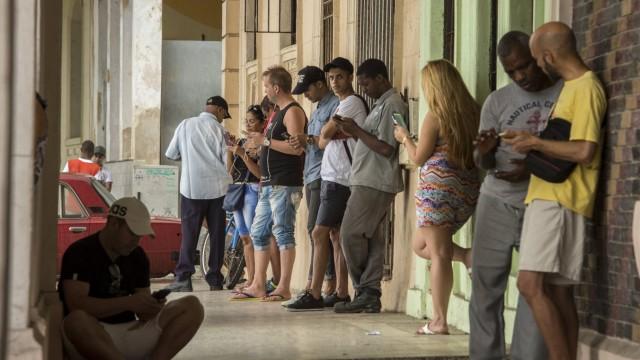Viele Menschen telefonieren mit dem Handy am Hotspot der Uferpromenade Malecon Kuba *** Many peopl