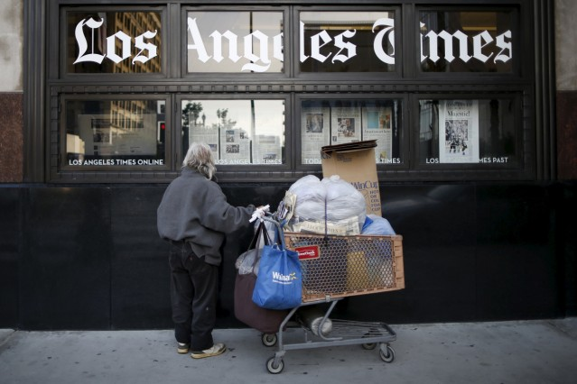 A homeless man reads the Los Angeles Times in the window of the building of Los Angeles Times newspaper, which is owned by Tribune Publishing Co, in Los Angeles