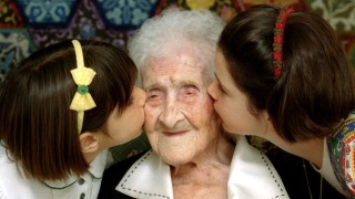 FILE PHOTO: The World's oldest woman, Jeanne Calment, 120 years old, is kissed by two young girls during a special ceremony in a retirement home in Arles