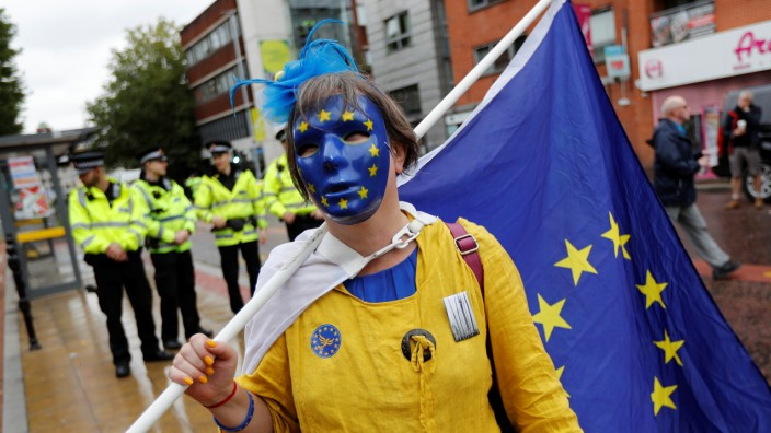 A demonstrator holds a European Union flag on the opening day of the Conservative Party Conference, in Manchester