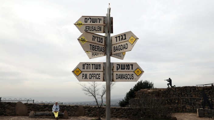 A woman sits near a sign at Mount Bental, an observation post in the Israeli-occupied Golan Heights that overlooks the Syrian side of the Quneitra crossing