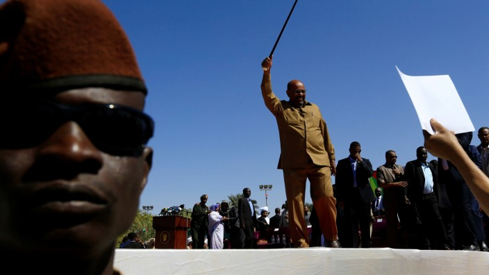 Sudan's President Omar al-Bashir waves to his supporters during a rally at the Green Square in Khartoum