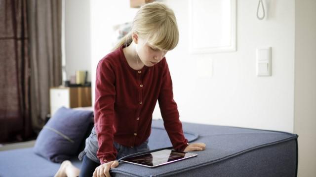 Ein Kind schaut sich etwas auf einem Tablet auf dem Sofa an Berlin 14 08 2018 Berlin Deutschland