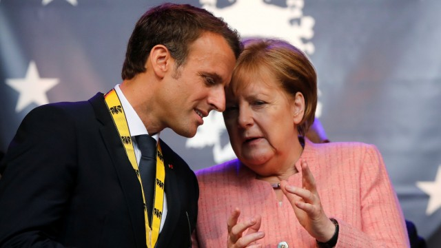 FILE PHOTO: French President Emmanuel Macron speaks with German Chancellor Angela Merkel after being awarded the Charlemagne Prize for 'European vision' in Aachen, Germany