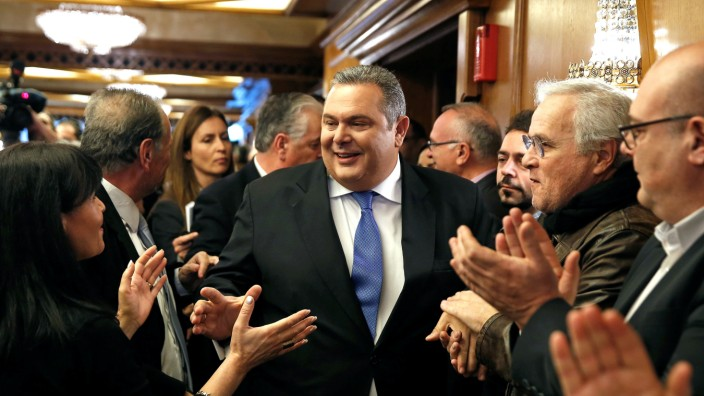 Panos Kammenos is applauded by his supporters as he arrives for a news conference in Athens
