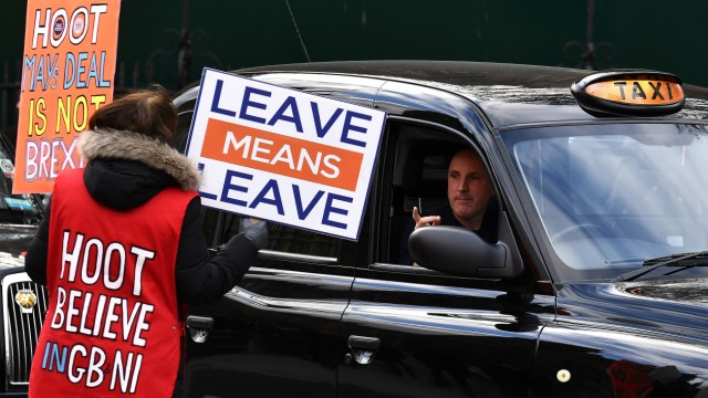 A pro-Brexit protester speaks to a taxi driver outside the Houses of Parliament in London