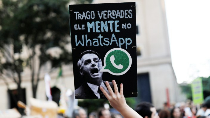A woman holds a sign with an image of presidential candidate Jair Bolsonaro during a protest in Sao Paulo