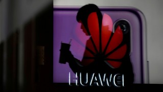 FILE PHOTO - A man walking past a Huawei P20 smartphone advertisement is reflected in a glass door in front of a Huawei logo at a shopping mall in Shanghai