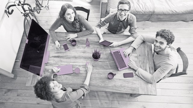 Elevated view of smiling coworkers working together at wooden table in office model released Symbolf