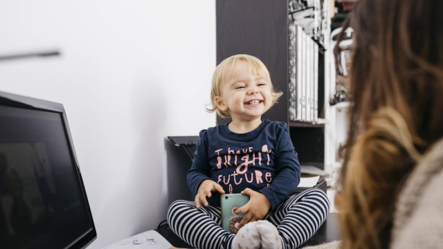 Mother working at home with little daughter sitting on desk model released Symbolfoto property relea