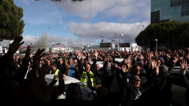 Taxi drivers raise their hands as they protest outside IFEMA fairgrounds during a taxi strike against regulation of ride-hailing and car-sharing services such as Uber and Cabify in Madrid