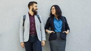 Smiling businessman and businesswoman with scooters leaning against a wall model released Symbolfoto