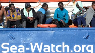 Migrants rest on board the Sea Watch 3 off the coast of Siracusa