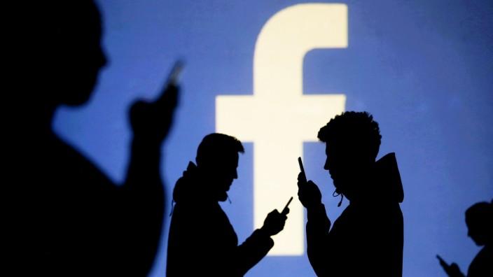 Facebook - Smartphone-Nutzer stehen vor dem Facebook-Logo